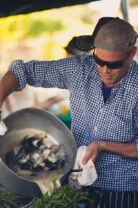 Chef Brian Malarkey pours clams and mussels into a dish.
